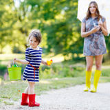 Mother and little adorable kid girl daughter in rain boots Stock Images