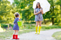 Mother and little adorable kid girl daughter in rain boots Stock Photos