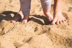 Mother and little baby feet on beach sand. Parent and child walking barefoot. Mother and cute little baby feet on summer beach sand. Family on the beach of Stock Images