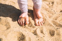 Mother and little baby feet on beach sand. Parent and child walking barefoot. Mother and cute little baby feet on summer beach sand. Family on the beach of Stock Photo