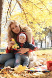 Mother and little baby girl playing under autumn tree Royalty Free Stock Images