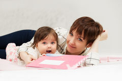 Mother and little baby girl reading a book on bed Royalty Free Stock Photo