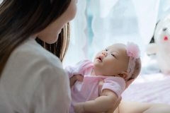 Mother and little baby laughing, playing together in bed room Stock Images