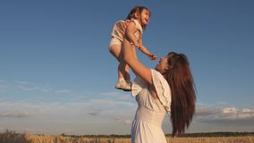 Mother and little baby play on field of ripe wheat. happy family travels. Mom throws up a happy daughter in the sky stock video
