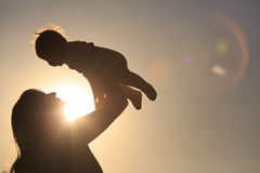 Mother and little baby play at sunset. Sky Royalty Free Stock Image