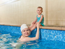 Mother and little baby at pool. Adorable baby girl enjoying swimming in a pool with her mother, early development class for infants teaching children to swim Royalty Free Stock Image