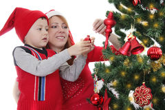 Mother and little boy as Santa helper decorating Christmas tree Stock Photos