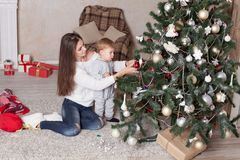 Mother and little boy at Christmas tree with gifts 1 Stock Photos