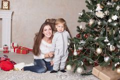Mother and little boy at Christmas tree with gifts 1 Stock Images