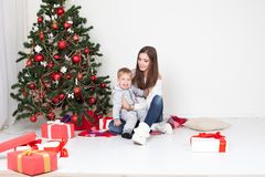 Mother and little boy at Christmas tree with gifts 1 Royalty Free Stock Image