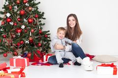 Mother and little boy at Christmas tree with gifts 1 Stock Photo