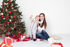 Mother and little boy at Christmas tree with gifts 1 Stock Photography
