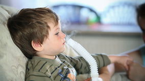 Mother and little boy inhaling medicine using nebulizer, stock footage Royalty Free Stock Photos