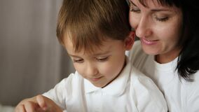 A mother and a little boy are looking intently at the tablet screen. A mother plays with her child using an app over the