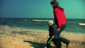 Mother and little boy running on the beach. Slow motion stock footage