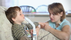 Mother and little boy using nebulizer to inhale medicine, stock footage Stock Photo
