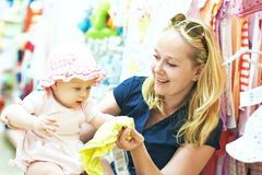 Mother with little child choosing baby apparel in shop. One year little child with mother choosing clothing in baby apparel store shop during outerwear shopping stock photos
