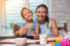 Mother and little child daughter cook at home. In the kitchen stock photo