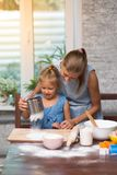 Mother and little child daughter cook at home. In the kitchen royalty free stock photos