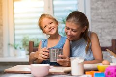 Mother and little child daughter cook at home. In the kitchen royalty free stock photography
