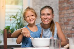 Mother and little child daughter cook at home. In the kitchen stock photos