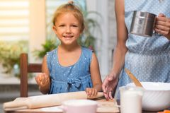 Mother and little child daughter cook at home. In the kitchen royalty free stock image