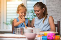Mother and little child daughter cook at home. In the kitchen stock photography