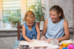 Mother and little child daughter cook at home. In the kitchen stock image