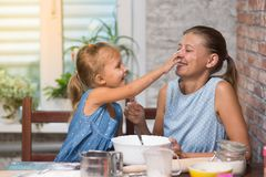 Mother and little child daughter cook at home. In the kitchen stock images