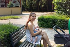 Smiling happy mother sitting on park bench and breastfeeding hungry baby boy. New mother holding and breastfeeding her little cute baby outside at public city stock image