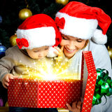Mother with little child opens the box with gifts on christmas Royalty Free Stock Image