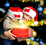 Mother with little child opens the box with gifts on christmas Stock Image
