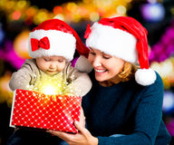 Mother with little child opens the box with gifts on christmas Royalty Free Stock Photos