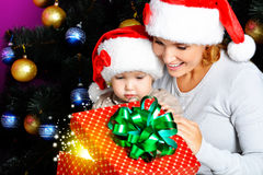 Mother with little child opens the box with gifts on christmas Royalty Free Stock Images