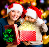 Mother with little child opens the box with gifts on christmas Royalty Free Stock Photography