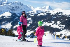 Mother and little child skiing in Alps mountains. Active mom and toddler kid with safety helmet, goggles and poles. stock photo
