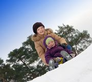 Mother with little child sliding in the snow Royalty Free Stock Photo