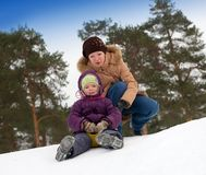 Mother with little child sliding in the snow Royalty Free Stock Image