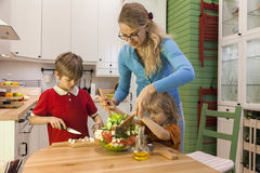Mother and little child stirring vegetable salad. Kids helping Mom on the kitchen Royalty Free Stock Image