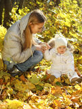 Mother with little daughter in autumn park Royalty Free Stock Photography