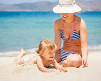 Mother with little daughter on the beach. Mother with little daughter playing on the beach Stock Image