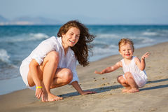Mother with little daughter on the beach Stock Images