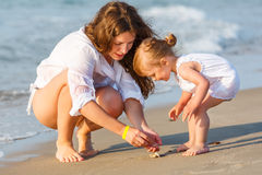 Mother with little daughter on the beach Royalty Free Stock Photo