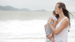 Mother with a little daughter on the beach with bad weather. stock video