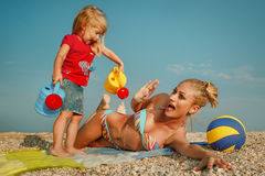 Mother with little daughter on the beach. Little girl on the beach have fun and laughing with her mother Stock Photos