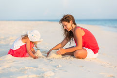 Mother with little daughter on the beach. Mother with little daughter playing on the beach Royalty Free Stock Photo