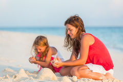 Mother with little daughter on the beach. Mother with little daughter playing on the beach Stock Images
