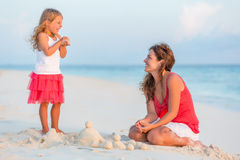 Mother with little daughter on the beach. Mother with little daughter playing on the beach Stock Photo