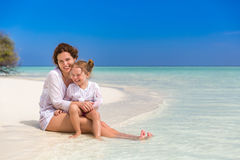 Mother and little daughter on the beach. Mother and little daughter playing on sunny beach Royalty Free Stock Photos