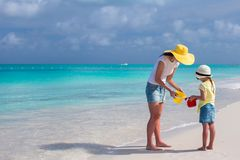 Mother and little daughter on the beach during their carribean vacation. Young mother walking with her little daughter during their carribean vacation Stock Photo
